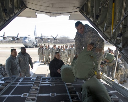 Soldiers from the 258th Field Artillery load bags onto a C130 aircraft during deployment training
