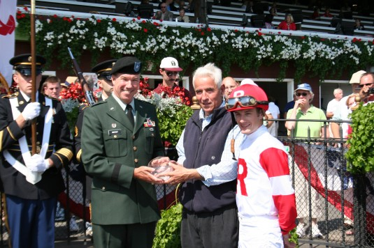 Brig. Gen. Michael Swezey presents the winner's trophy to the owner and jockey for Heartache, winner of the third race at Saratoga on Sep. 2.