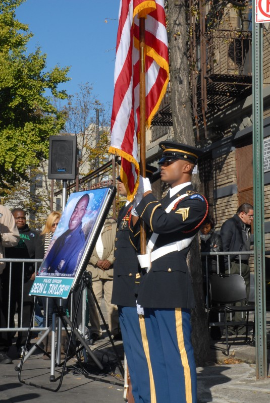 A military forces honor guard stands next to a portrait of fallen New York Army National Guard Sgt. Deon Taylor
