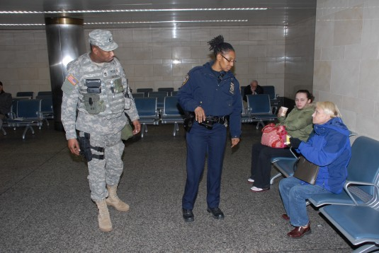 New York Army National Guard Sgt. 1st Class David Peeler from the 101st Signal Battalion assists Metropolitan Transit Authority (MTA) Police Officer Bailey in Penn Rail Station