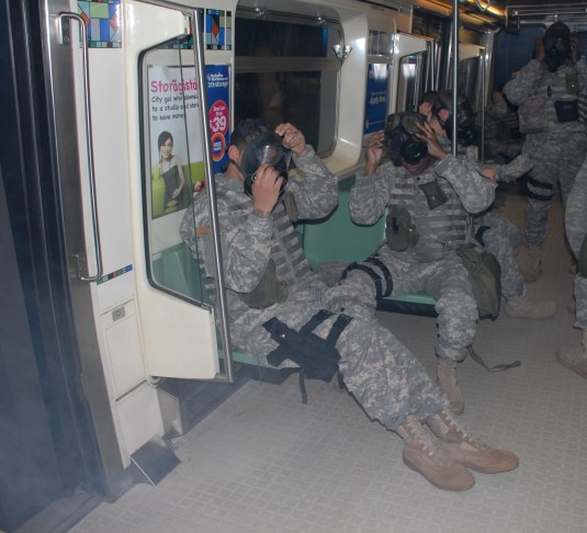 Soldiers don protective masks as smoke fills the subway car during training with the MTA