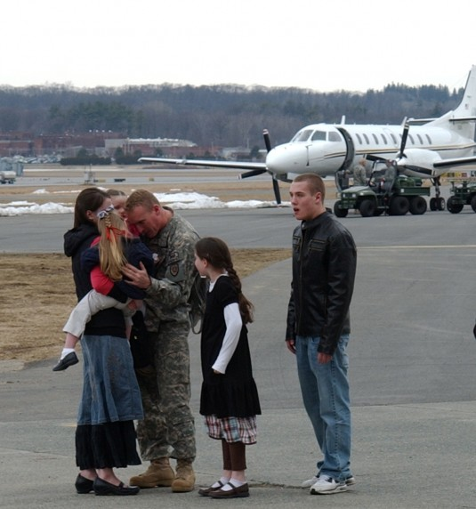 Soldier embraces his family