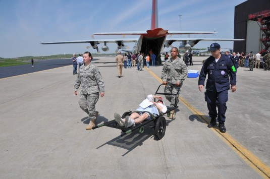 Medics moving simulated casualty from plane