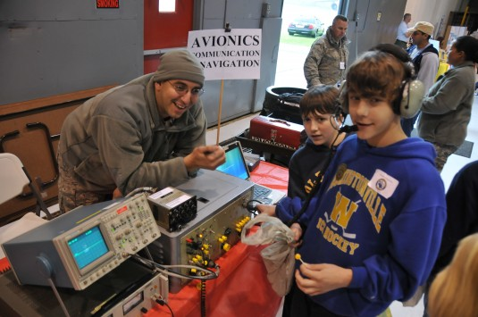 Airman working with kids and electronics