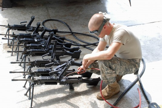 Soldier cleaning machine guns