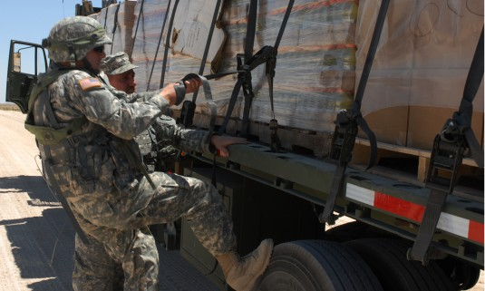 Soldiers tying down truck load