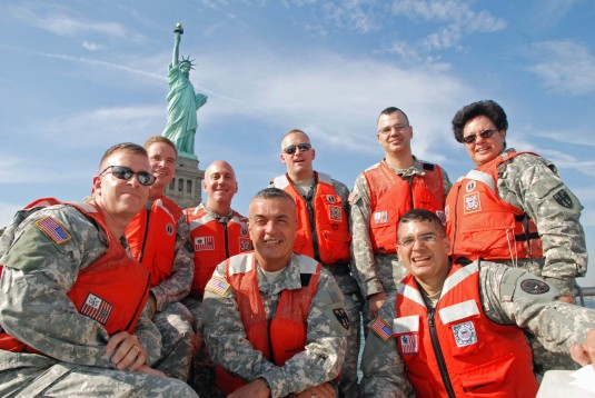 Officers pose in front of Stature of Liberty