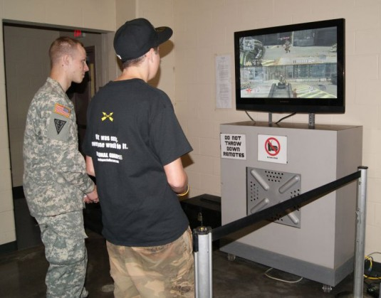 A member of the NY National Guard's 466th Area Medical Support Company competes with a visitor during the Queensbury Interactive Game Experience Sept. 11.