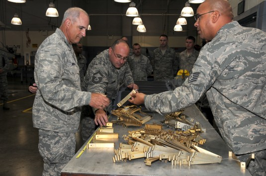 Mechanic demonstrates brackets to Air Force General