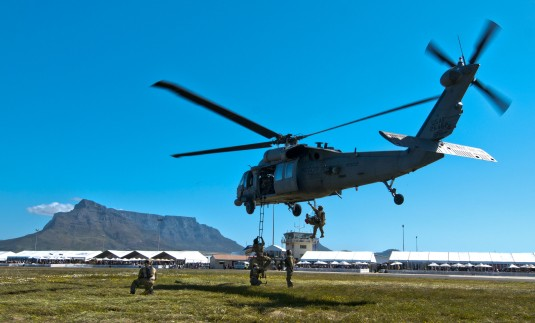 Airman climbing into hovering helicopter