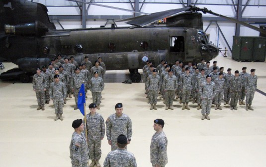 Soldiers in formation in hanger in front of helicopter
