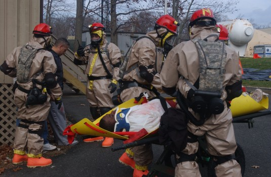 Army National Guard Soldiers in hazard suits evacaute a casualty during a training exercise.