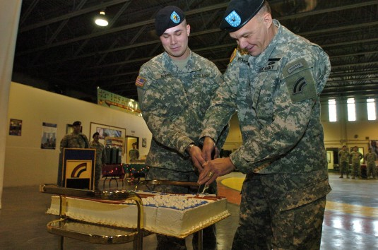Brig. Gen. Steven Wickstrom and Pvt. 1st Class Kevin Adams cut into a celebratory birthday cake for the National Guard.