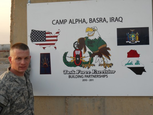 Lt. Col. Rob Mitchell poses next to battalion's headquarters sign.