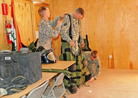 Soldiers helping Major General Eddy Spurgin try on EOD Suit