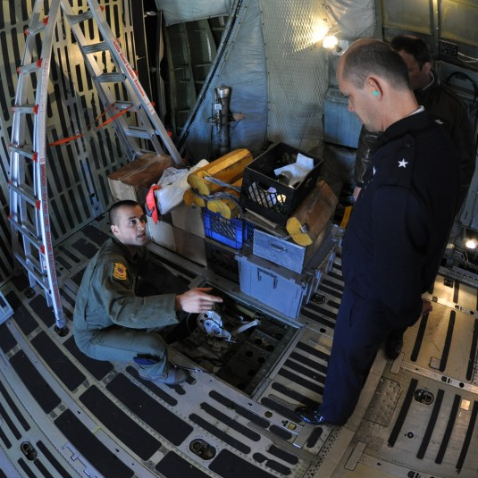 Airman 1st Class James Segretti, describes operating powered winches to support cargo loads onto C-5A Galaxy strategic airlifters to Brig Gen Daniel Bader