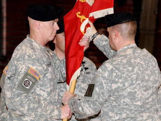 New York Army National Guard Lt. Col. James Freehart, left, a veteran of Afghanistan, receives the unit colors from Lt. Col. Jim Pabis