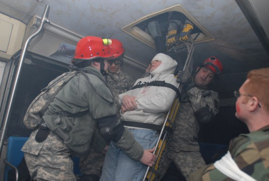 Soldiers pull the mock victim through a hatch in the bus roof