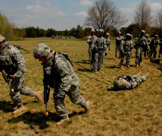 Two Soldiers haul a simulated casualty on a sled.