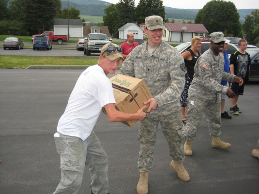 New York Army National Guard Spc. Matthew Greenberg, a truck driver with the 719th Transportation Company, based in Harlem, hands a case of water to Michael Kissinger, a local volunteer to help aid people affected by Hurricane Irene here during the Nation
