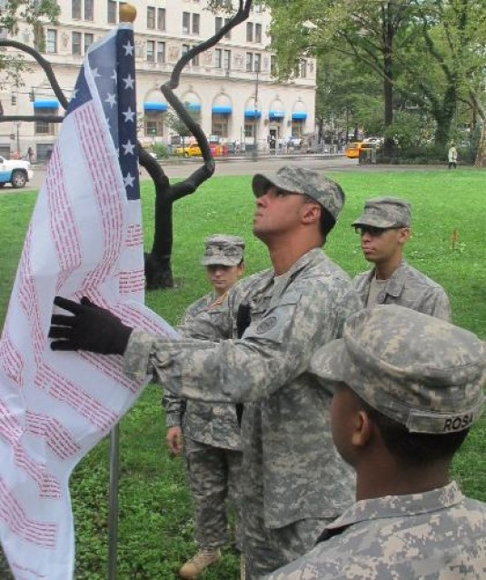 Soldiers placing commemorative flag