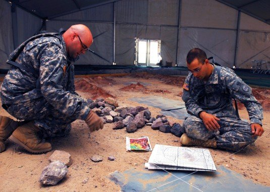 Sgt. Luke Zuercher (left) and Spc. Ryan Blount from the 27th Infantry Brigade Combat Team use maps, rocks and sand to create a sand table