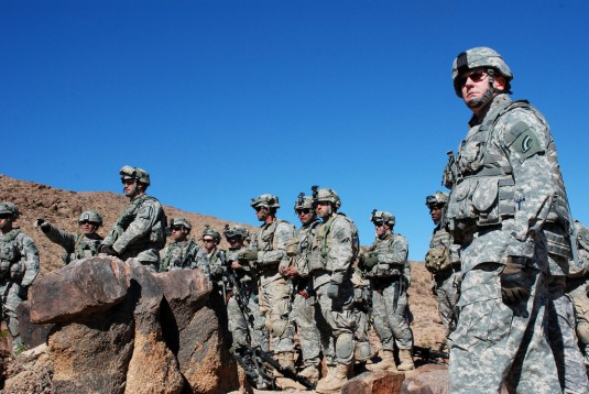 Soldiers standing on ridgeline in the desert.