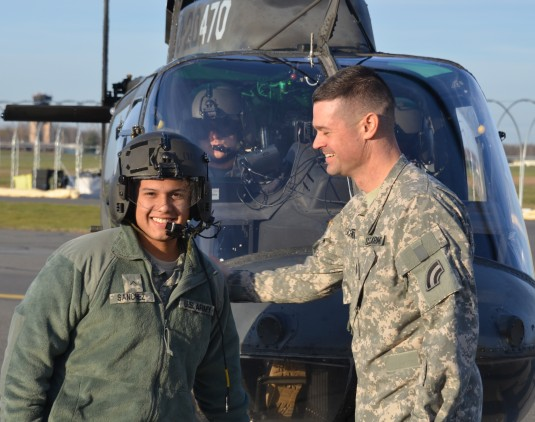 Soldier gets congratulated on promotion in front of OH-58 helicopter.
