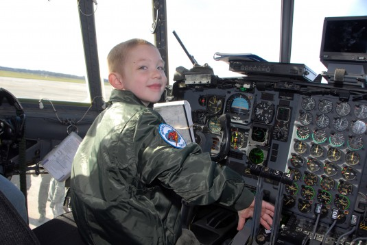 Youngster sits in C-130 cockpit.