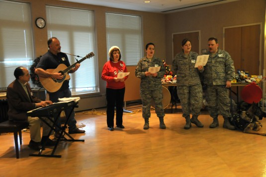 Air Guardsmen sing carols at Veterans Administration Center.