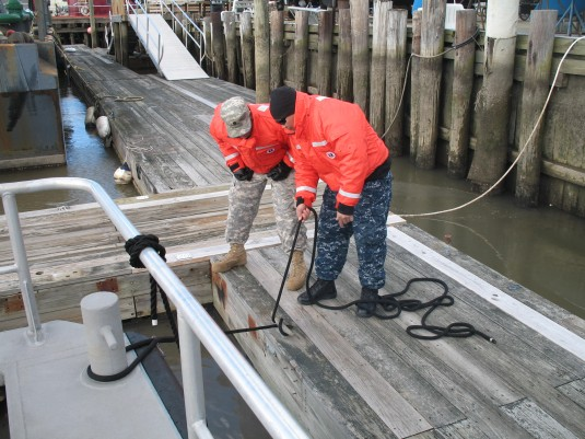 NAval Militia members instructs National Guard Soldier on boat mooring techniques.
