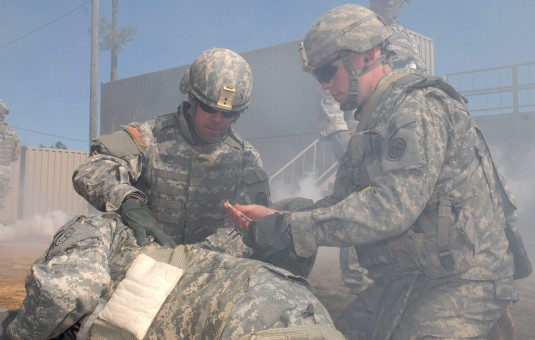 Sgt. Andrew Brechko, left, and Spc. Travis Wood, right, treat a mock casualty at a casualty collection point during combat lifesaver training here on Feb. 11. Brechko belongs to Headquarters and Headquarters Company, 27th Infantry Brigade Combat Team, and