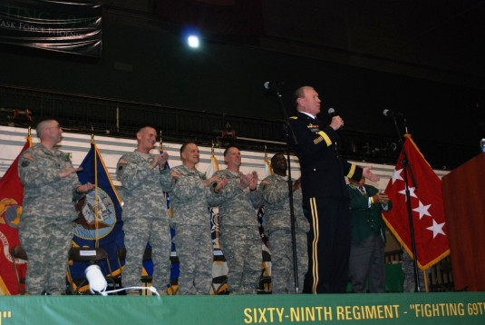 General Martin Dempsey, the Chairman of the Joint Chiefs of Staff leads members of the New York Army National Guard's 1st Battalion 69th Infantry in a chorus of