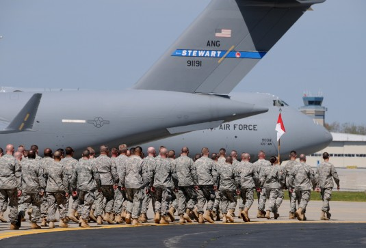 Soldiers of the Army Reserve's 411th Engineering Brigade marches past the 105th Airlift Wing's aircraft ramp to a passenger holding area April 19, 2012 following their deployment ceremony at the base.