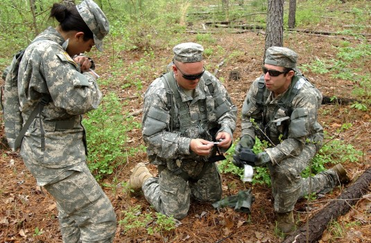 New York Army National Guard 1st Lt. Amy Bonilla (right), Sgt. Keith Burd and Spc. Matt Cordaro from 3rd Battalion, 142nd Assault Helicopter Battalion,  orient themselves in the woods before trekking to a clear landing area for a UH-60 Blackhawk during Pe