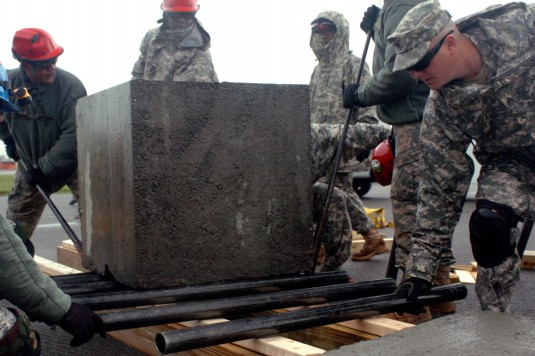 New York Army National Guard Sgt. John Grace, member of the 1156th Engineer Company&rsquot;s Search and Extraction Team, places a roller in front of a two-ton block as it moves 75 feet past obstacles at the New York State Preparedness Center, May 14, 2012