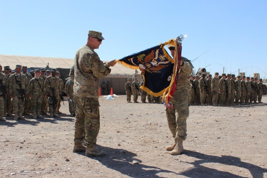 Lt. Col. Joseph Bieler, right, and Command Sgt. Maj. David Oliver, of the Army National Guard's 2nd Battalion, 108th Infantry, uncase the battalion colors