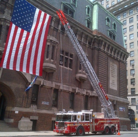 A giant American flag hoisted between two Fire Department New York trucks marks the front door of the New York State Division of Military and Naval Affairs Lexington Avenue Armory on Wednesday, June 6.