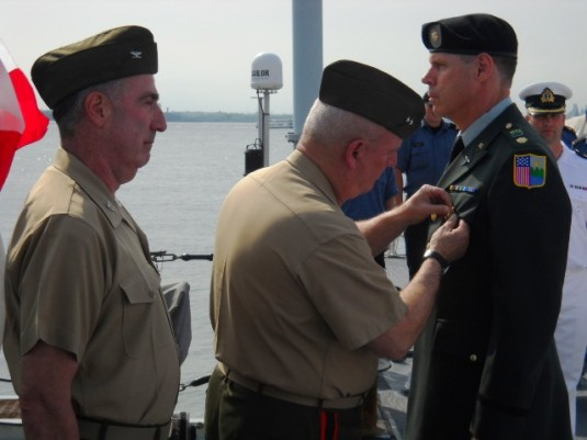 Major General Robert Wolfe, the commander of the New York Naval Militia, presents the New York State Defense of Liberty Medal to New York Guard Major Michael Lonski on May 23.