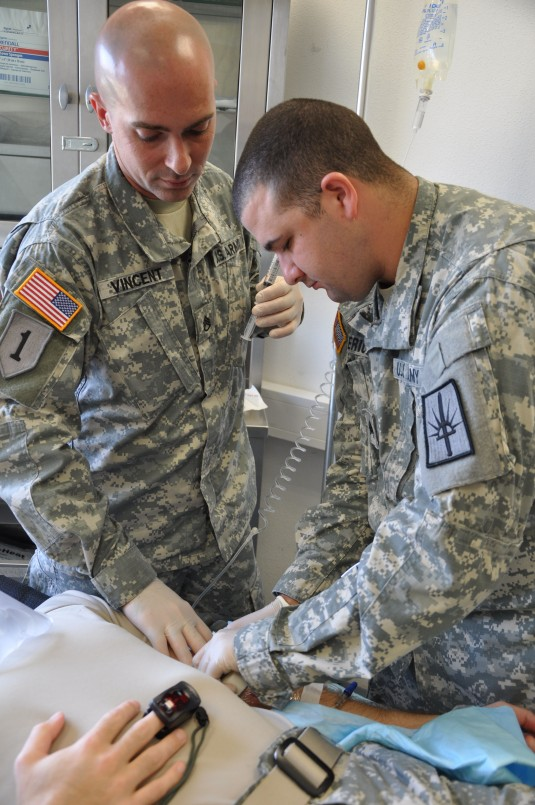 New York Army National Guard Sgt. 1st Class William C. Vincent and Sgt. Michael P. Boulerice, medics with the 466th Area Support Medical Company from Queensbury, administer an IV to a patient at the Joint Multinational Readiness Center medical clinic here