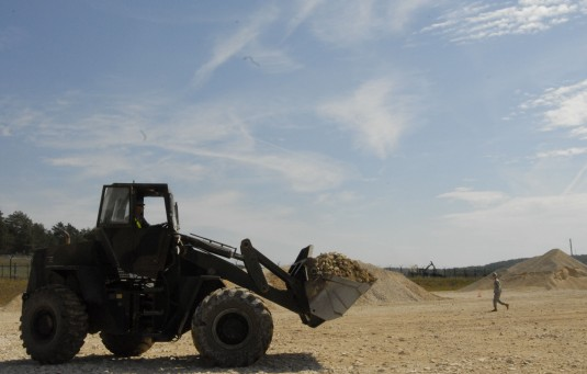 A construction vehicle transports gravel to deposit on the helicopter landing zone at the Joint Multinational Readiness Center here, August 15, 2012.