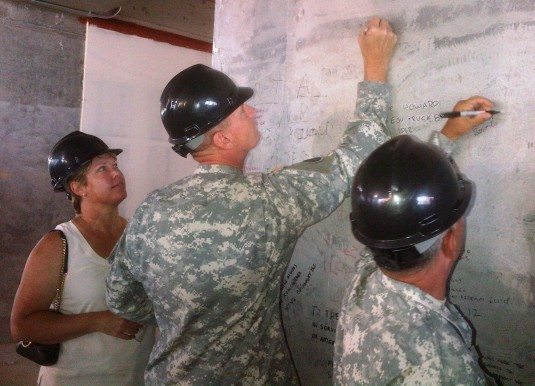 Major General Patrick Murphy, the Adjutant General of New York, (center) scrawls his name on a wall on the 39th floor of the Freedom Tower under construction at the World Trade Center location here on Wednesday, August 29.
