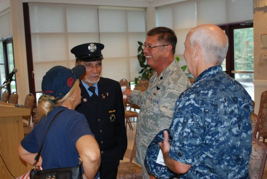 New York Air National Guard Lt. Col. Steven Fukino, center, and New York Naval Militia Lt. Commander Don McKnight speaks with former New York City fireman Bill Massena