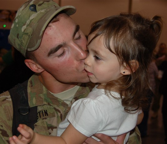 New York Army National Guard Spc. Josh Austin gives his daughter, Jaida, a kiss upon returning home from Afghanistan with the 2nd Battalion, 108th Infantry Regiment September 26, 2012.