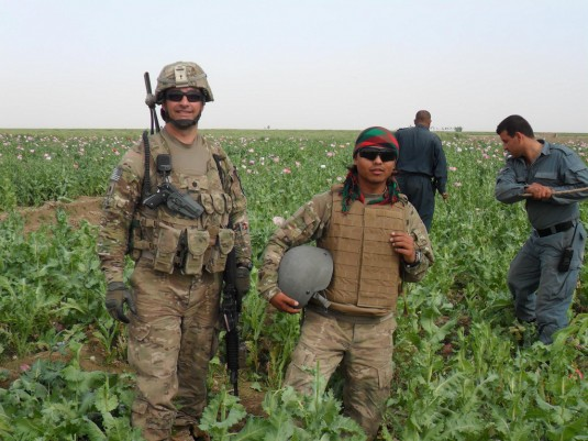 Lt. Col. Russell Clark (left), poses with his interpreter in an opium poppy field as Afghan National Police (ANP) use sticks to hack off the plants' seed pods