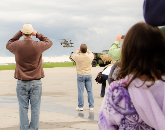 Family members of 43 Soldiers assigned to  F Co. 1-169 General Support Aviation Battalion watch as the unit's UH-60 Blackhawks make their final fly over on their way to Ft. Hood, Texas on Saturday, Sept. 29.