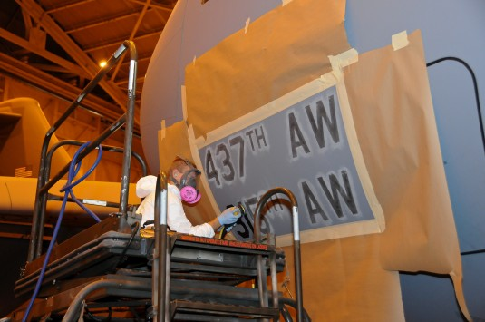 New York Air National Guard Staff Sgt. Brian Burns prepares nose area  of C-17 Tail Number 10188, formerly assigned to Charlestown Air Force Base, for  painting  with 105th Airlift Wing  markings on Wednesday, October 10.