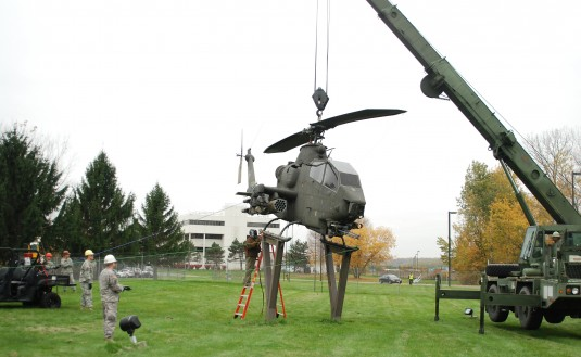 New York Army National Guard Soldiers assigned to the 827th Engineer Company prepare to hoist the AH-1S Cobra attack helicopter displayed in front of Division of Military and Naval Affairs headquarters off its pedestal on Thursday, Oct. 25.