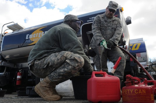 STATEN ISLAND--Army Sgt. Adama Ilbouda, left, with the New York Army National Guard, and Tech. Sgt. David Tayler, with the New York Air National Guard's 274th Air Support Operations Squadron, distribute fuel at the Staten Island Armory, Saturday, No