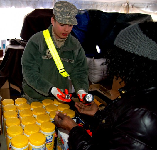 Pfc. Mimmo Pirrone, an aircraft structural repairer with Company B, 642nd Aviation Support Battalion, distributes flashlights and batteries to local residents
